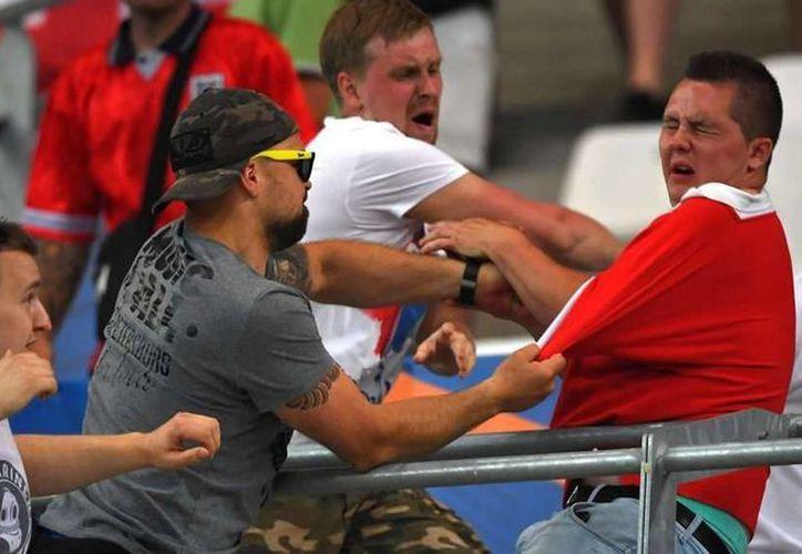 Imagen de un grupo de aficionados rusos golpeando a un inglés en el partido Inglaterra vs Rusia, de la Eurocopa 2016, que se realizó en Marsella. (DPA)