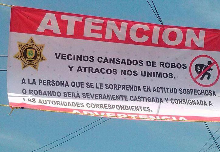 La manta que los vecinos del fraccionamiento Jacinto Canek colgaron de los postes, y que el domingo por la noche bomberos y policías bajaron. (Especial)