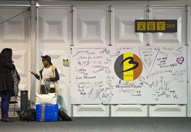Dos mujeres conversan junto a un mural como tributo a las víctimas de los atentados en el aeropuerto de Zaventem, cerca de Bruselas, Bélgica. (EFE)