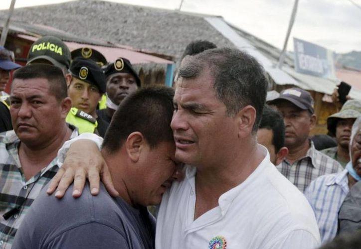 El presidente de Ecuador, Rafael Correa. llora abrazado a uno de los vecinos de Canoa, duramente castigada por el terremoto. (AP)