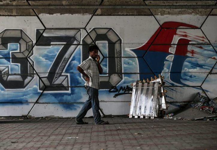 Un hombre camina junto a un mural del vuelo desaparecido de Malaysia Airlines en Shah Alam a las afueras de Kuala Lumpur, Malasia. (Archivo/EFE)