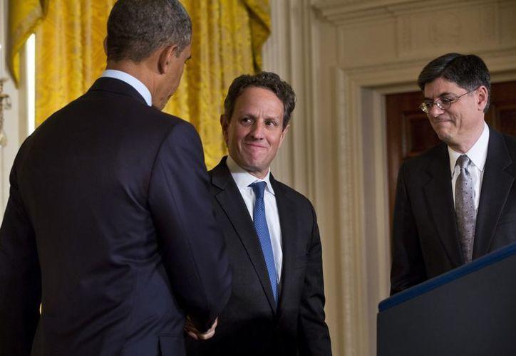 Obama (i), felicita por sus servicios al saliente secretario del Tesoro, Tim Geithner, en presencia de su sucesor, Jack Lew, en la Casa Blanca de Washington. (EFE)