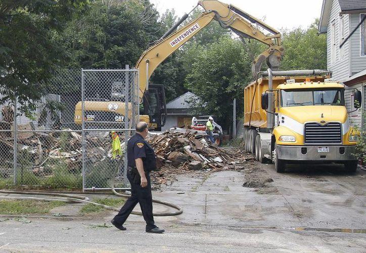 Un policía observa la demolición de la casa del secuestrador y violador Ariel Castro en la avenida Seymour, en Cleveland, Ohio, EU. (EFE)