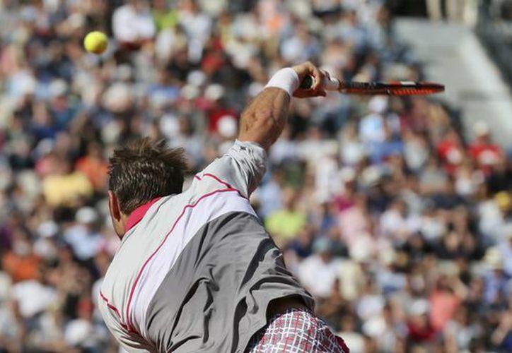 El suizo Stanislas Wawrinka hizo historia este martes en Francia al eliminar por primera vez en un Grand Slam a su compatriota Roger Federer y avanzar a semifinales de este torneo por vez primera. En la foto, Wawrinka ejecuta un servicio. (Foto: AP)