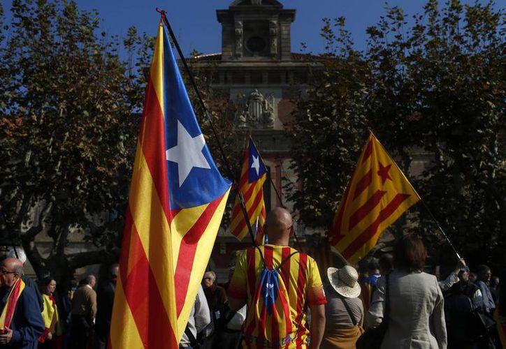 Unas personas ondean una Estelada, el nombre por el que se conoce a la bandera independentista catalana, afuera del Parlamento catalán. (Agencias)