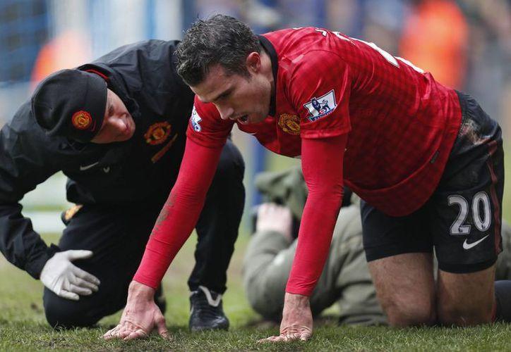El holandés Robin van Persie salió lesionado, luego de chocar con un fotógrafo. (Agencias)