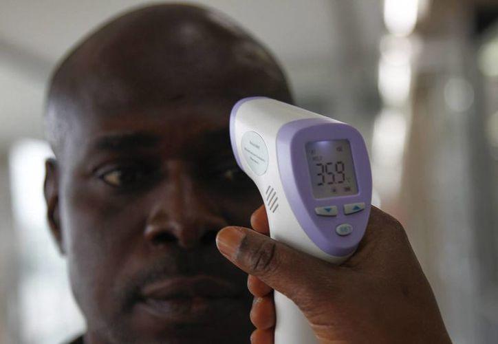 Un voluntario del Instituto Nacional de Salud Pública mide la temperatura de los viajeros a su llegada a Congo como precaución sobre el ébola. (EFE/Archivo)
