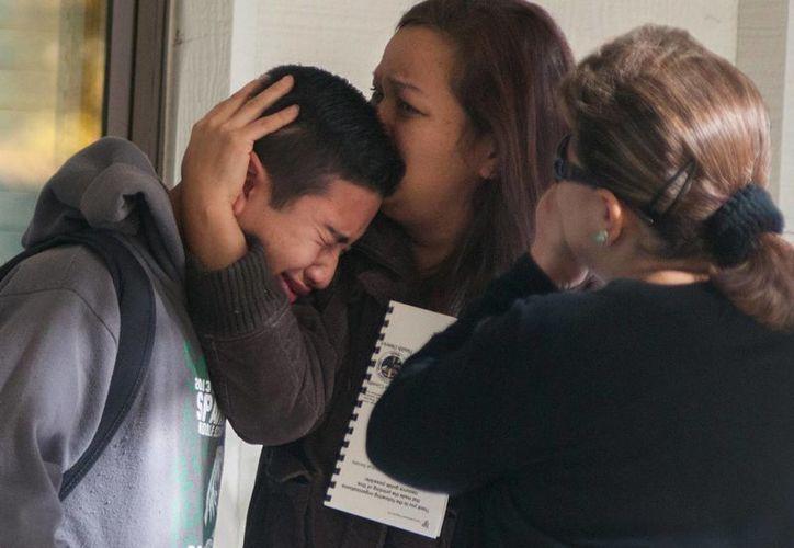 Los padres abrazan a sus hijos llorosos en un centro de evacuaciones. (Agencias)