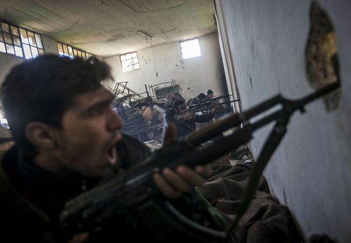 Combatientes del Ejército Sirio Libre disparan contra fuerzas del gobierno en una academia militar en el norte de Alepo. (Agencias)