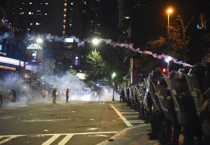 Varios manifestantes se encaran a policías antidisturbios durante las protestas ocurridas anoche por segundo día consecutivo en Charlotte, Carolina del Norte. (EFE)