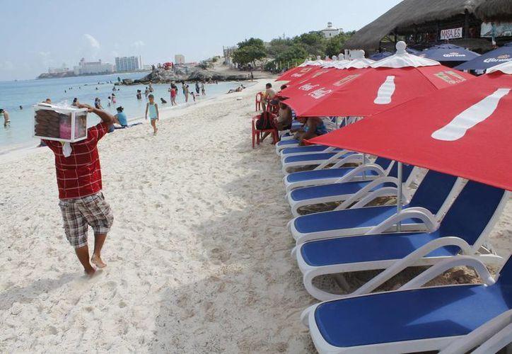Pese a los operativos, algunos ambulantes se arriesgan a vender en las playas. (Jesús Tijerina/SIPSE)