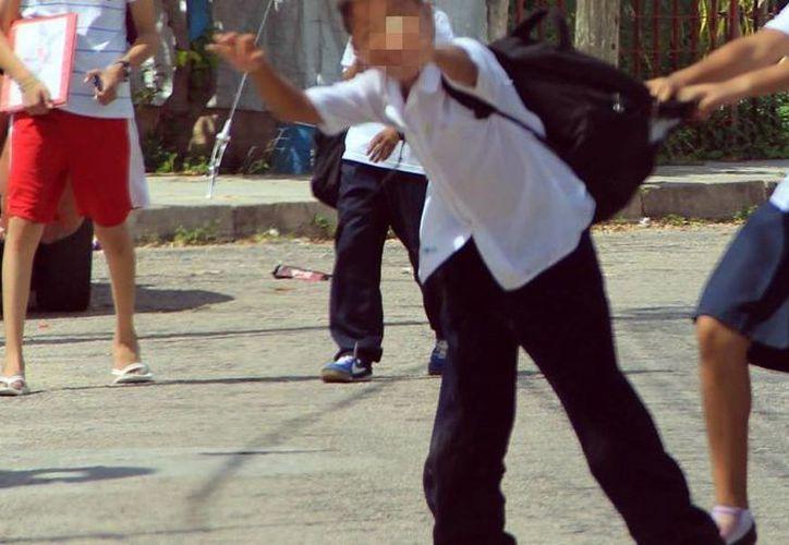 Un joven con discapacidad soportó bullying por parte de sus compañeros en la preparatoria. El caso ha llegado a instancias penales. En la imagen, de contexto, un grupo de niños agreden a otro menor. (Archivo/Milenio Novedades)
