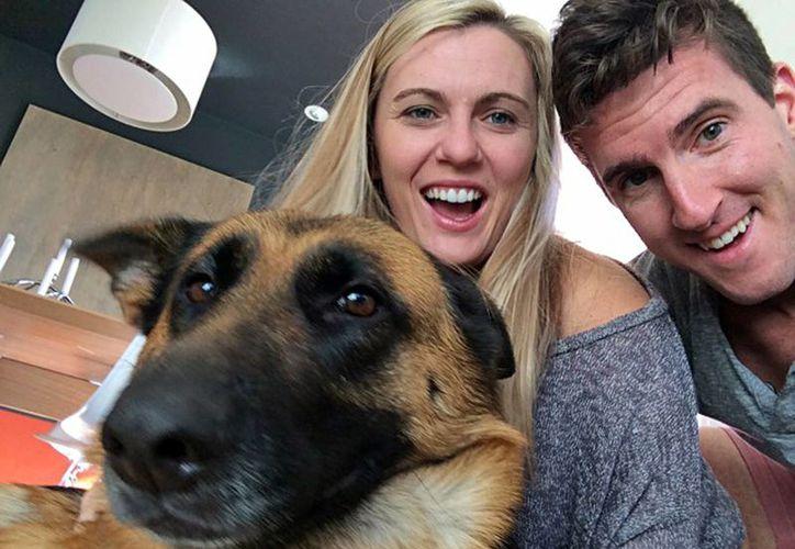 Katie Sullivan y James Marquis con la perra Octavia, un pastor alemán de dos años que adoptaron durante el Teletón canino del Día de Acción de Gracias en Estados Unidos. (AP)