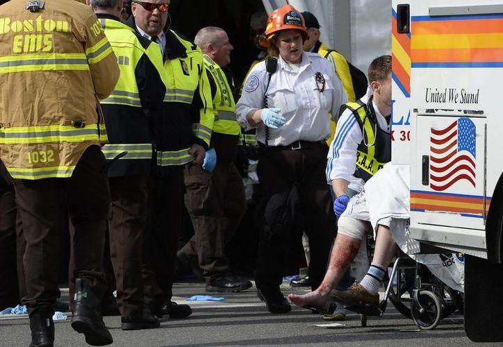 Un hombre herido es trasladado a una ambulancia después de que se registraran dos explosiones cerca a la línea de meta. (EFE)