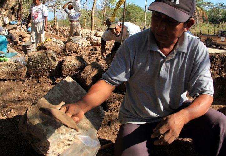 Con cautela, los trabajadores extraen los pedazos de cerámica. (SIPSE)