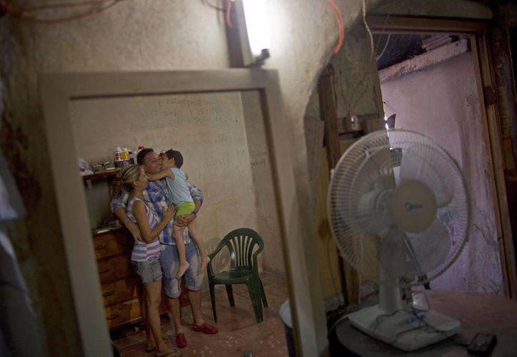 Un día después de su liberación, Wilberto Parada, de 42 años, con su hijo y esposa, son vistos reflejados en un espejo durante una entrevista en su casa en La Habana, Cuba. (Agencias)