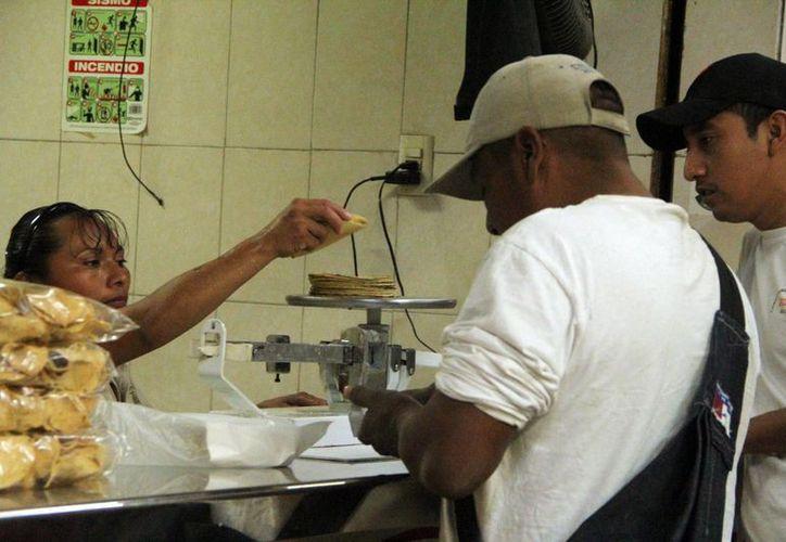 El costo del kilo de tortilla varía de 12 a 15 pesos. Una vendedora  atiende clientes en una tortillería en Yucatán. (Milenio Novedades)