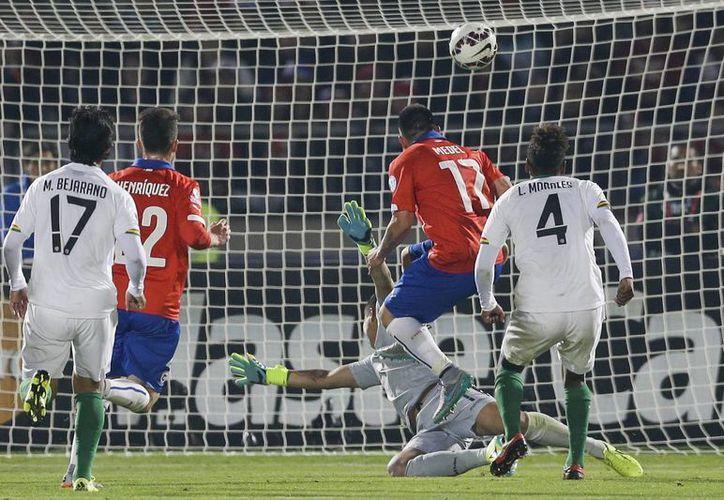 Gary Medel (segundo desde la derecha) anota uno de los tantos de Chile, que ganó 5-0 sobre Bolivia y clasificó como primero del Grupo A a cuartos de final. (Foto: AP)
