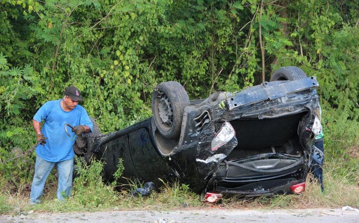 El auto en el que viajaban cuatro jóvenes se salió del camino y quedó volcado, en la carretera Mérida-Valladolid. (Aldo Pallota/SIPSE)