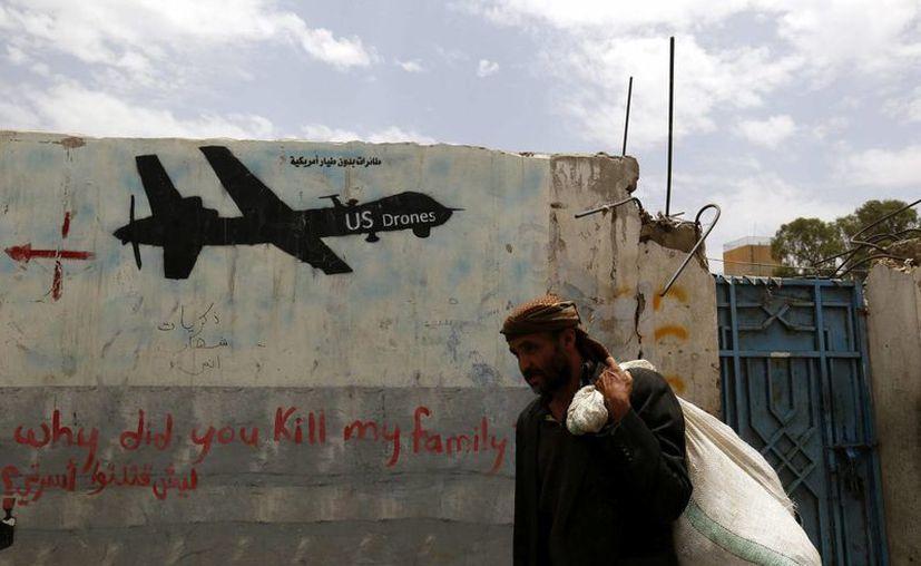 Dos hombres fueron ejecutados acusados de espionaje por miembros de Al Qaeda. Imagen de un yemení que camina a lo largo de una pared en la que aparece el graffiti de un drone estadounidense, en Saná, Yemen. (EFE/Archivo)