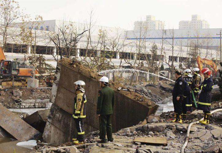 Miembros de los servicios de emergencia trabajan en el escenario de una explosion registrada el pasado mes de noviembre en la ciudad costera de Qingdao, China. (Archivo/EFE)