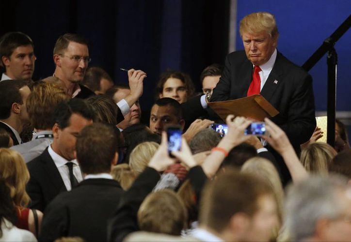 Donald Trump firma autógrafos tras el debate de aspirantes presidenciales republicanos en el teatro Milwaukee, el martes 10 de noviembre de 2015, en Milwaukee. (Foto AP/Morry Gash)