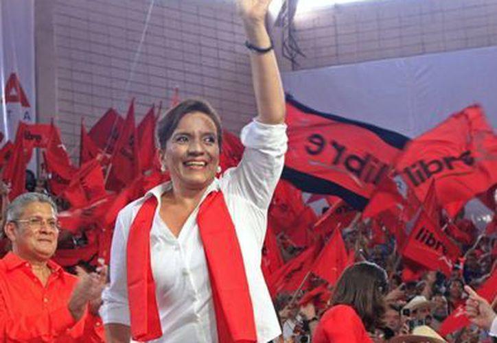 Xiomara Castro, candidata a la presidencia de Honduras y esposa del derrocado mandatario Manuel Zelaya, saluda a sus seguidores en una convención del Partido Libre. (Agencias)