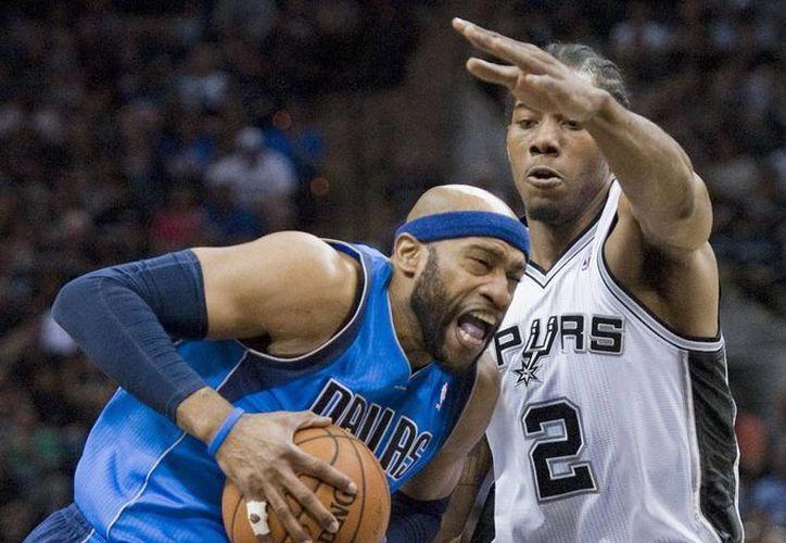 El jugador de San Antonio Spurs, Kawhi Leonard (d), intenta parar una entrada a canasta de Vince Carter, de Dallas Mavericks, en los cuartos de final de conferencia en el AT&T Center en San Antonio. (EFE)