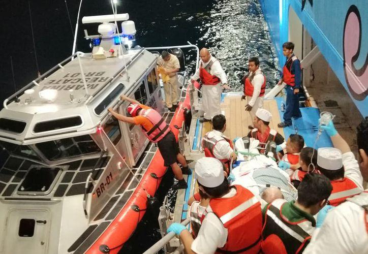 Elementos de la SEMAR realizaron una maniobra de evacuación médica del tripulante del crucero frente a la costa de Isla Mujeres. (Cortesía)