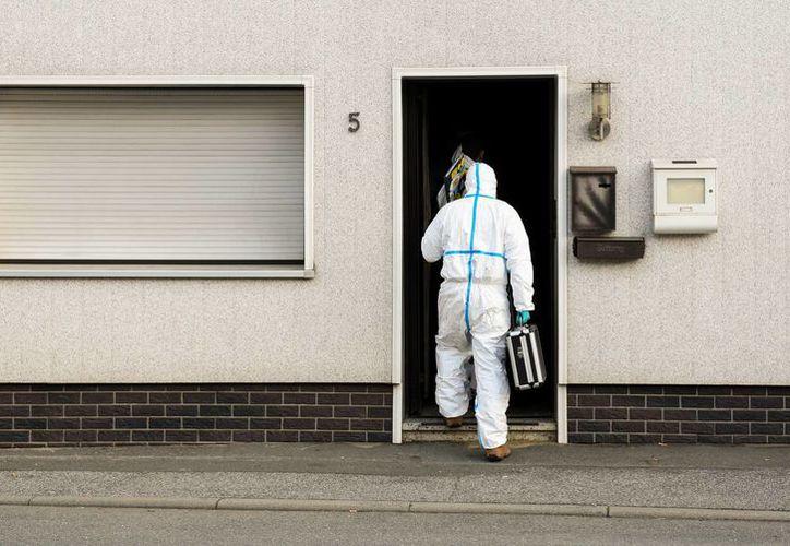 Detectives con trajes herméticos entran a una casa en Wallenfels, Alemania, donde ocho bebés muertos fueron hallados, el 13 de noviembre del 2015. (Nicolas Armer/dpa via AP)