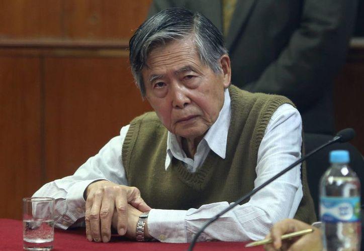 Fujimori escuchó cabizbajo la decisión del juez, cogiéndose el brazo izquierdo con la mano derecha cuyo pulgar movía constantemente. (Agencias)