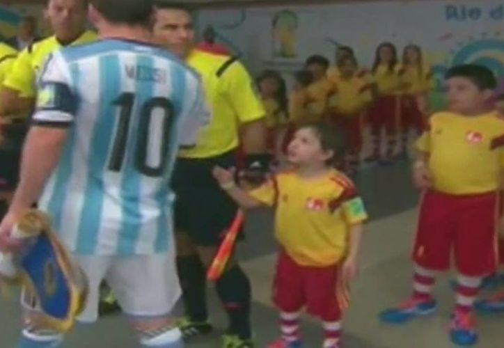 Messi avanza junto a un niño que le extiende la mano sin obtener respuesta del goleador de Argentina en el Mundial. (Captura de pantalla de You Tube)