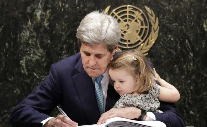 El secretario de Estado de EU, John Kerry, detiene a su nieta Isabel Dobbs-Higginson mientras firma el Acuerdo de París sobre el cambio climático. (Agencias)