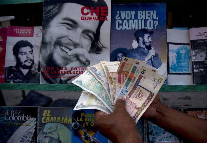 Un vendedor de libros posa con pesos cubanos (izq) y pesos convertibles (los cuatro a la derecha), en La Habana.