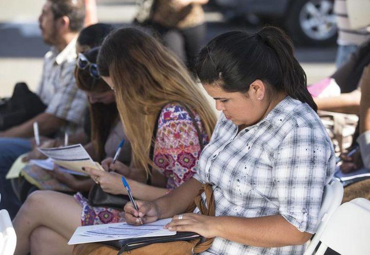 El desempleo en los hombres se ubicó en 3.6 por ciento en septiembre pasado y en las mujeres avanzó de 3.9 por ciento en agosto a 4.1 por ciento en septiembre de 2016. Imagen de unas jóvenes sentadas mientras llenan una solicitud de empleo. (Notimex)