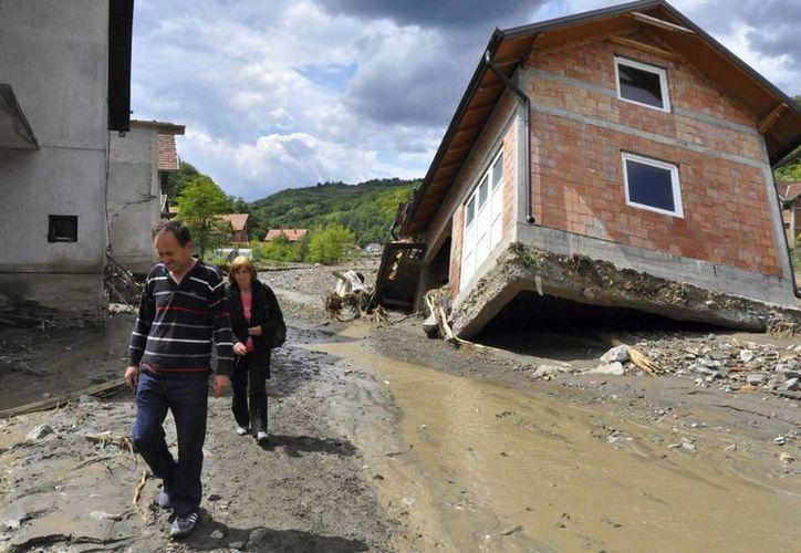 Una pareja pasa por delante de una vivienda afectada tras las inundaciones que azotaron Krupanj, al sureste de Belgrado, Serbia. (EFE)