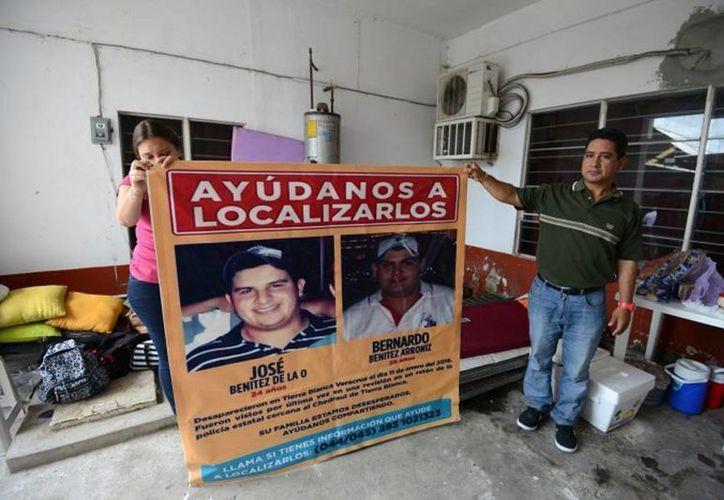 Imagen de los familiares de dos de los jóvenes desaparecidos en Tierra Blanca, Veracruz, sosteniendo una manta con la fotografía de  José Benítez de la O y Bernardo Benítez Arroniz. (veracruz.mx)