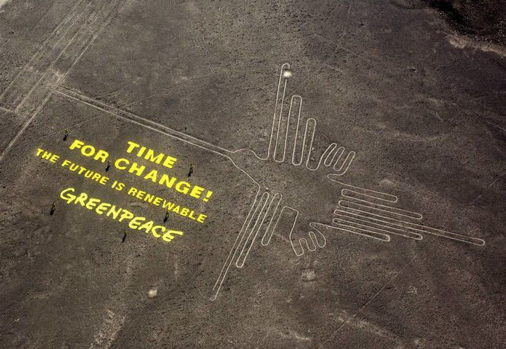 """En esta foto del 8 de diciembre de 2014, activistas de Greenpeace se colocan al lado de inmensas letras amarillas en las que se puede leer """"Tiempo de cambiar! El futuro es renovable"""", escritas cerca las líneas de Nazca, en Perú. (Foto: AP/Rodrigo Abd)"""