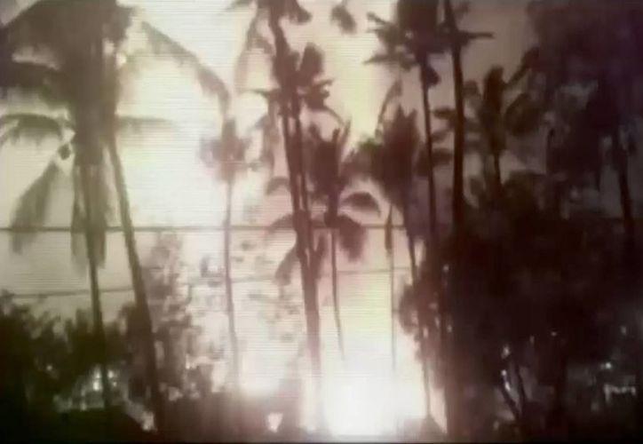 En esta imagen tomada de un video, se puede ver el destello producido por la explosión que se ve al fondo, durante un espectáculo de fuegos artificiales en un templo de Kollam, en el estado sureño de Kerala, India, en la madrugada de este domingo. (KK Productions via AP Video)