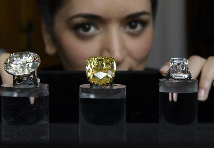 Una empleada de Sotheby's muestra (de I a D) un diamante de talla brillante considerado como el más grande del mundo de su categoría, el diamante Graff Vivid Yellow, de 100.09 kilates, y el diamante Victoria. (EFE)