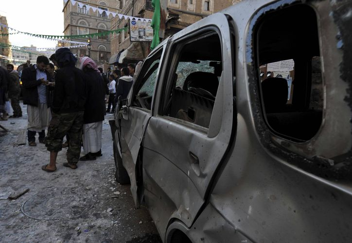Policías y chiíes observan el lugar donde se produjo una explosión contra la casa de un miembro del movimiento chií hutí en Saná (Yemen), el pasado 23 de diciembre. (EFE)