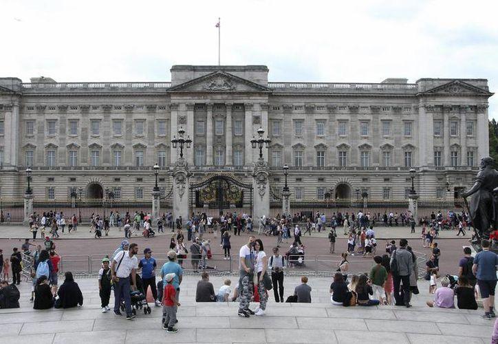 Fotografía de turistas que se encuentran enfrente del palacio de Buckingham en Londres. Este martes un hombre brincó la cerca del Palacio de Buckingham. (AP Foto/Leonora Beck)
