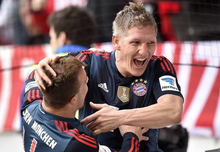 El Bayern Munich vivió 82 minutos de 'angustia' no sólo por no poder meterle gol a Mainz, sino porque éste lo dominó por momentos. En la foto, Schweinsteiger (de frente) celebra con Xherdan Shaqiri el primer gol del trabuco dirigido por Pep Guardiola. (Agencias)
