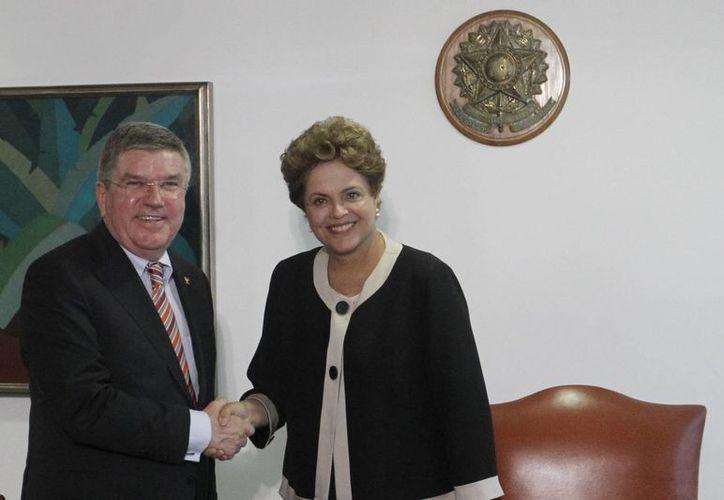 La mandataria brasileña Dilma Rousseff (d) estrecha la mano del presidente del Comité Olímpico Internacional (COI), Thomas Bach (i), este 24 de febrero, durante una reunión en Brasilia, Brasil. (EFE)