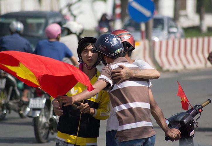 Dos manifestantes se abrazan, después de realizar diversos disturbios. (Agencias)