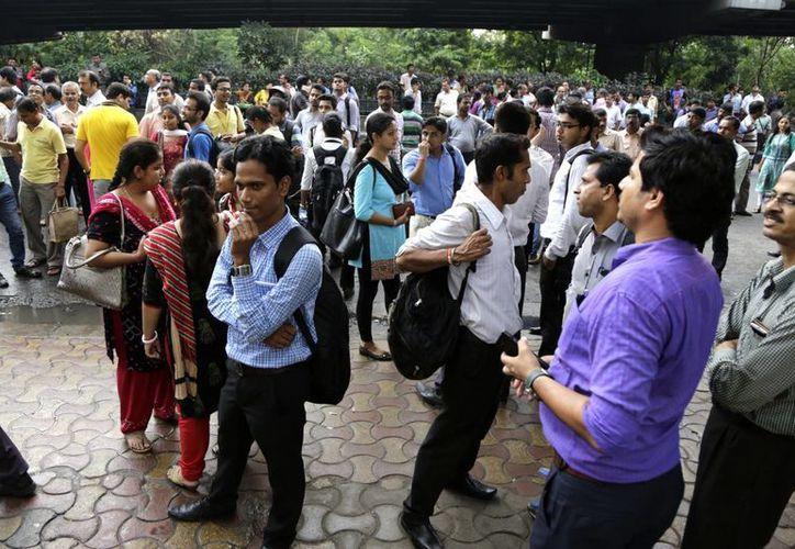 La gente se coloca al aire libre después de que salieron de sus oficinas tras el temblor que se registró. (AP/Bikas Das)