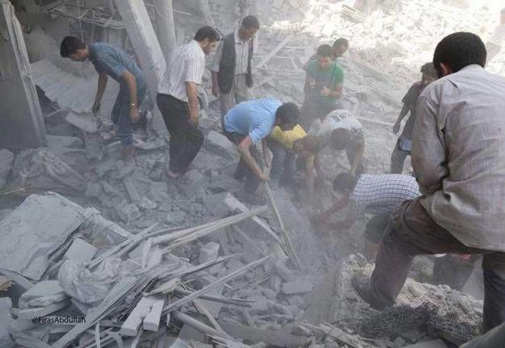 En imagen, sirios buscando sobrevivientes bajo los escombros de un edificio en Damasco. Decenas de muertos han dejado diversos ataques en la región, la cual es controlada por rebeldes. (AP)