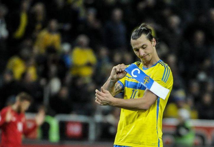 Zlatan Ibrahimovic, de la selección sueca, se quita la banda de capitán al finalizar partido de repechaje contra Portugal para la clasificación a Brasil 2014. (EFE)