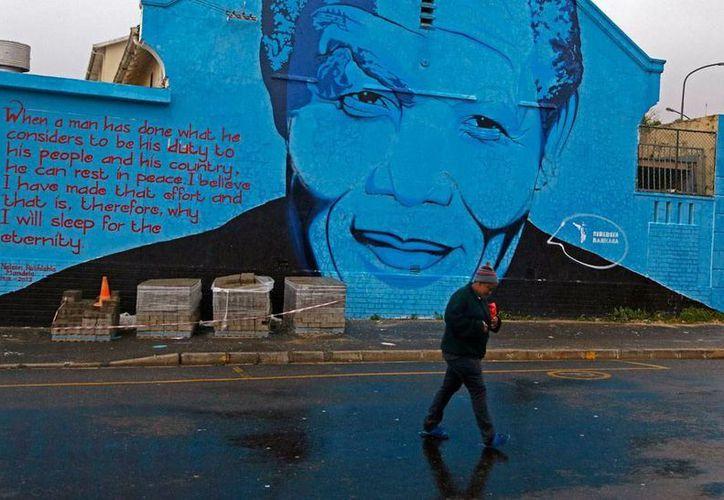Una mujer camina frente a un mural del rostro del desaparecido expresidente de Sudáfrica, Nelson Mandela, -en cuyo honor se celebran hoy varios actos en el mundo- en Cape Town. (AP)