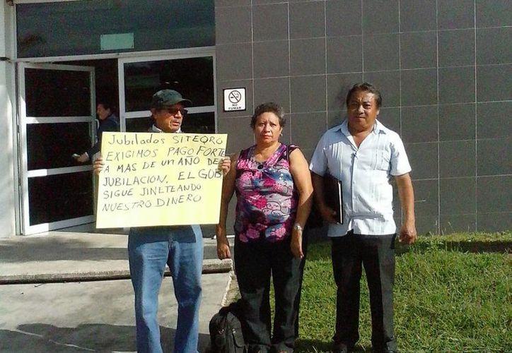 Los maestros jubilados exigen el pago de su fondo de ahorro en las oficinas de la SEyC. (Harold Alcocer/SIPSE)